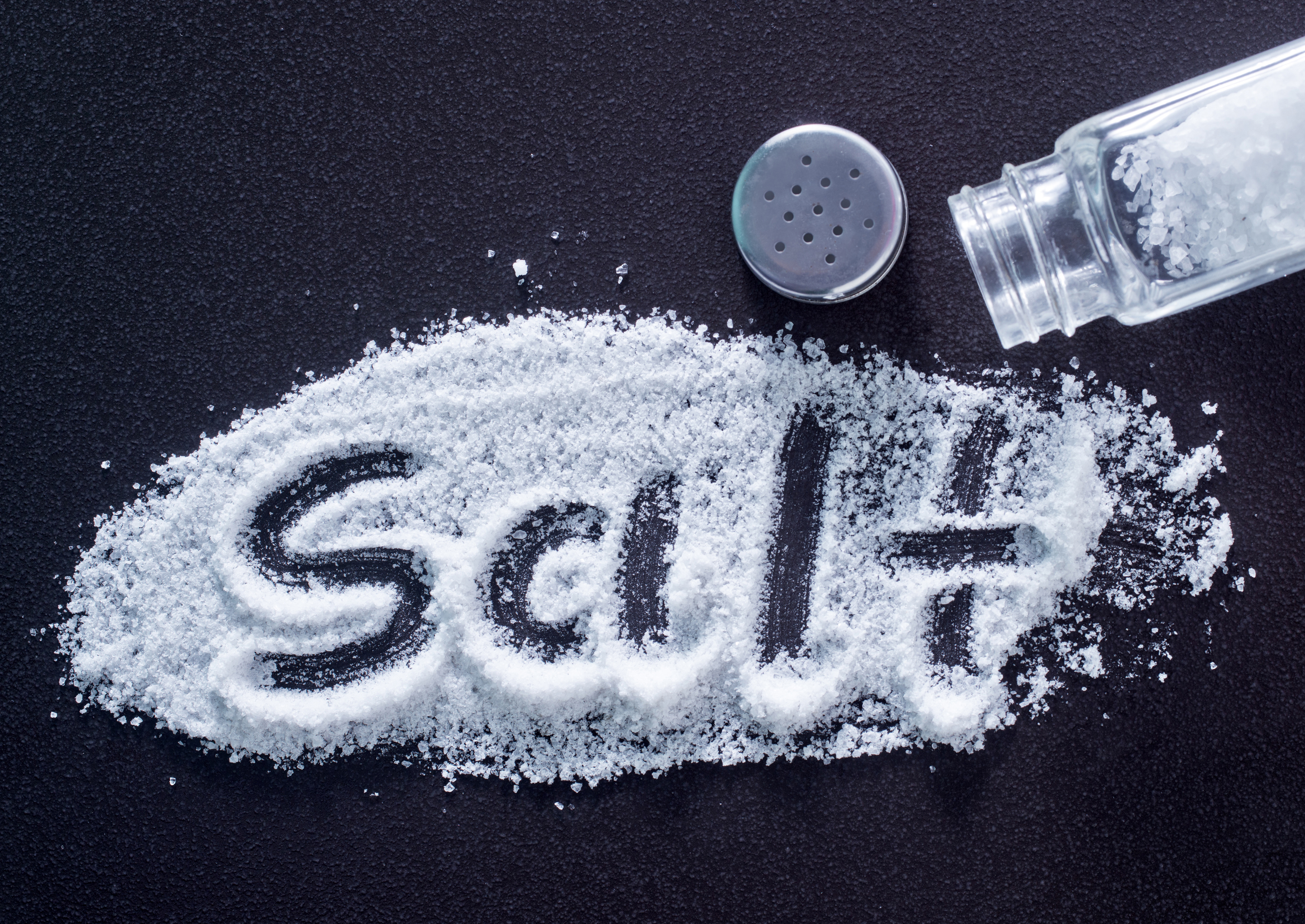 white sea salt in bottle and on a table