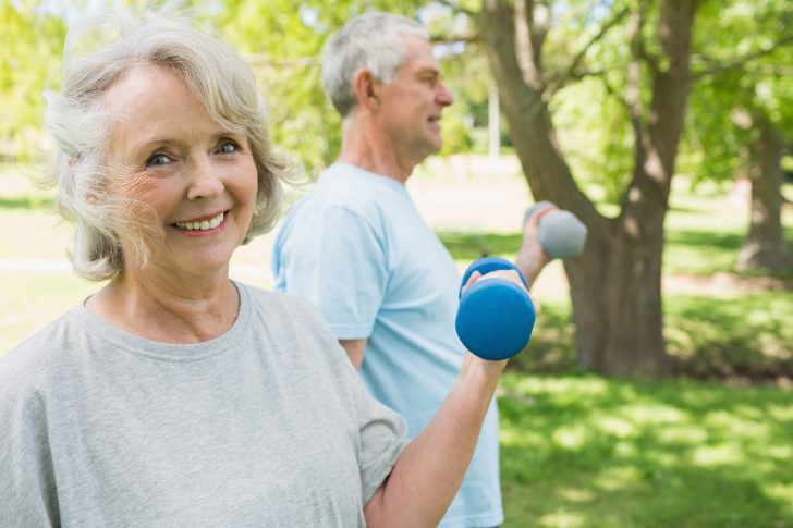 Portrait of a mature couple using dumbbells at the park