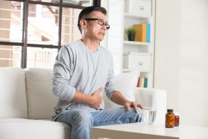 asian senior with stomach pain and medicine
