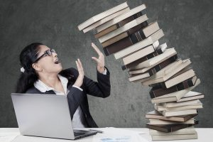 Portrait of worried businesswoman holds a pile of falling books over gray background